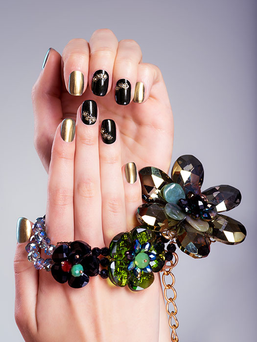 Beautiful woman's nails with  creative manicure and jewelry